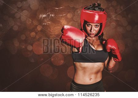 Portrait of pretty boxer with fighting stance against dark background
