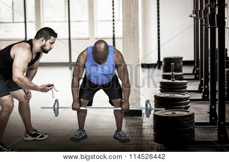 Man lifting barbell with trainer against barbell disc plates arranged