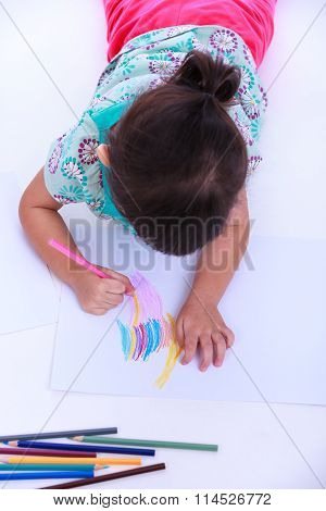 Top View. Child Lie On The Floor And Drawing On Paper.  On White