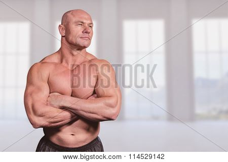 Muscular fit man with arms crossed against room overlooking ocean
