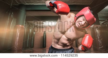 Aggressive boxer against black background against red boxing area with punching bags