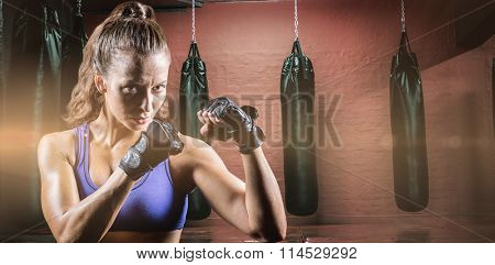 Portrait of female confident boxer with fighting stance against punching bags in red boxing area