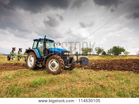 Blue tractor and dramatic sky.