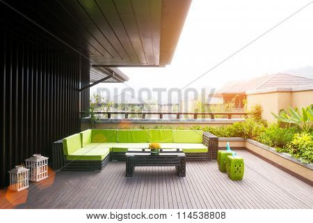 elegant bench and table on wooden floor outside house with sunbeam