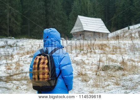 Back side of backpacker man walking to old traditional Carpathian log cabin in Polish Tatra Mountain