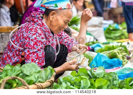Ethnic counting money selling vegetables at market
