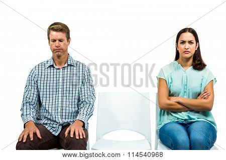 Sad couple not talking after argument on white background