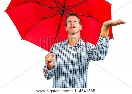 Man checking weather while holding red umbrella against white background