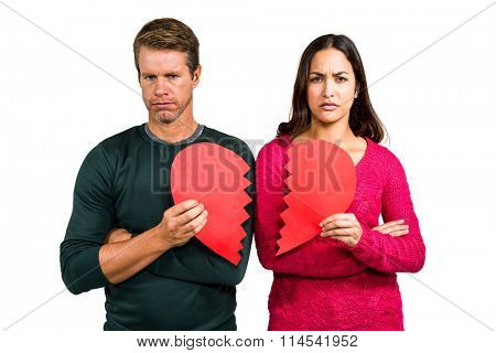 Portrait of serious couple holding cracked heart shape on white background