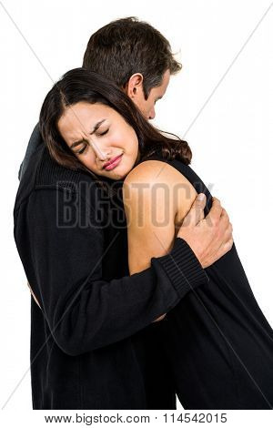 Unhappy couple embracing against white background