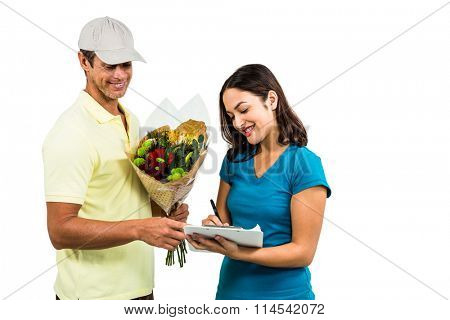 Happy flower delivery man taking signature of beautiful woman against white background