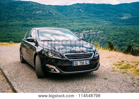 Black colour Peugeot 308 car on background of French mountain na