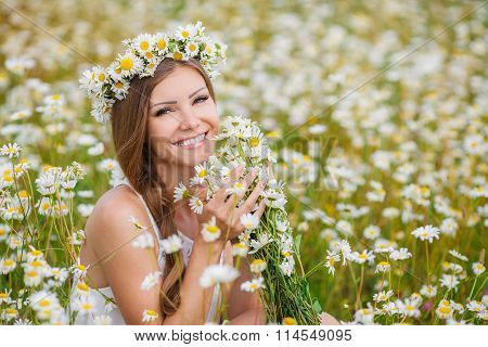 Beautiful young woman in a field of blooming daisies
