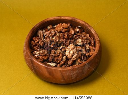 Walnut Kernels In Wooden Plate On Yellow Background