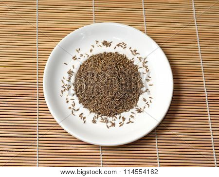 Spices In A White Plate On Bamboo Mat, Top View
