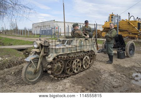 Members of military-historical club in the form of a German soldier and motorcycle-tractor