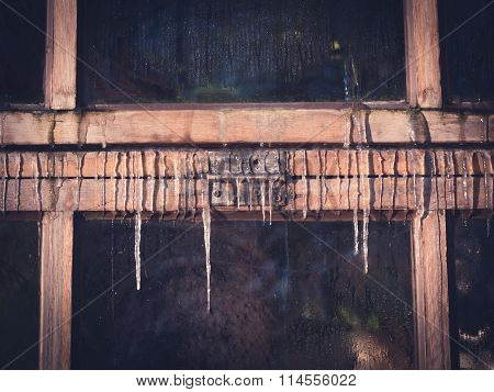 Icicles on Old Wooden Window Front View