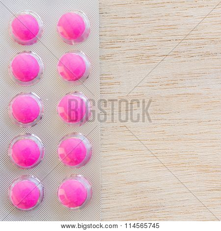 Pink pills in blister pack on wooden background
