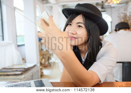 Young Asian Woman Sitting At Cafe Drinking Coffee And Taking Selfportrait