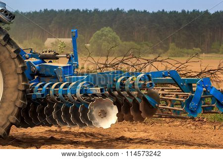 Cultivator On Ground Road By Ploughed Field Against Village