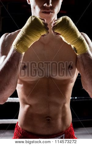 Skillful young boxer is showing his fists