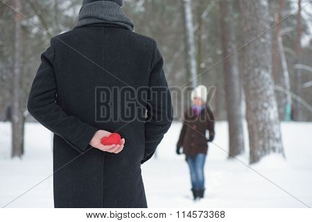 Confession of Love. Concept of Valentines Day. Surprise to woman. Man hiding behind a decorative heart