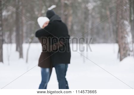 Embrace of couples in love. Romantic date in winter park. Photo in defocusing