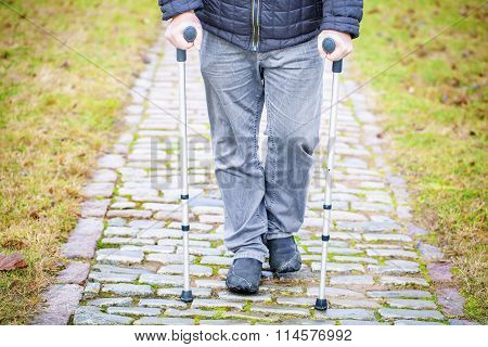 Disabled veteran on crutches at cemetery
