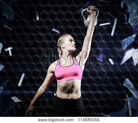 Muscular woman lifting heavy kettlebell against glass shattering to show dark pattern