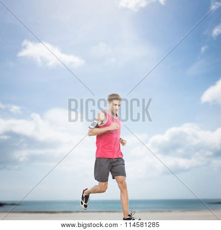 Fit man running against beach