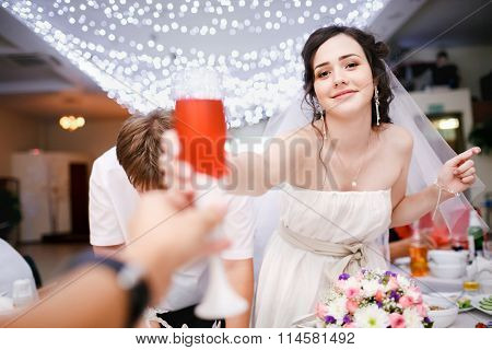 Beautiful young bride in white dress playfully raised glass of champagne and want to make a toast, c