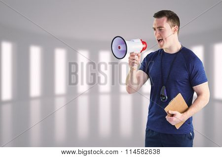 Male trainer yelling through the megaphone against bright room with windows