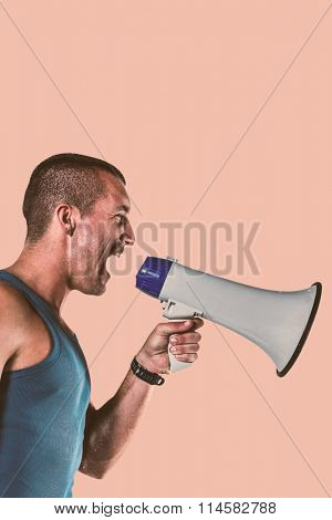Angry male trainer yelling through megaphone against orange background