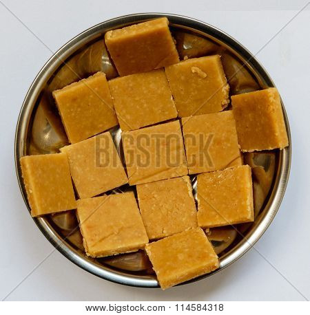 Traditional Indian sweet called cashew burfi kept in a bowl on a plain background