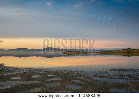 Winter landscape with lake and sunset fiery sky