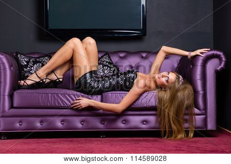 woman wearing a short dress relaxing on sofa