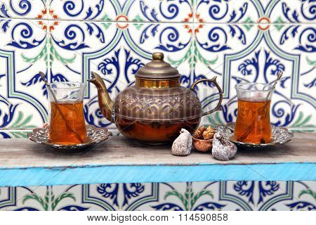 Vintage Arabic teapot with two Arabic glasses full of tea on metal saucers near the walnut and figs