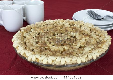 Home made apple pie with designer custom embossed flower design crust on a red table cloth