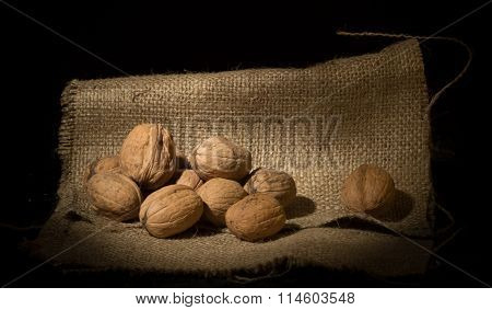 Walnut kernels and whole walnuts on rustic sack.