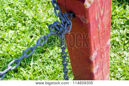 Red Fence Post With Tied Metal Chain Against Grass