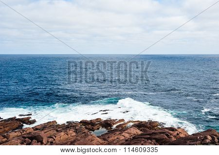 Water And Waves Splashing On Rocky Ocean Coast Under Cloudy Sky