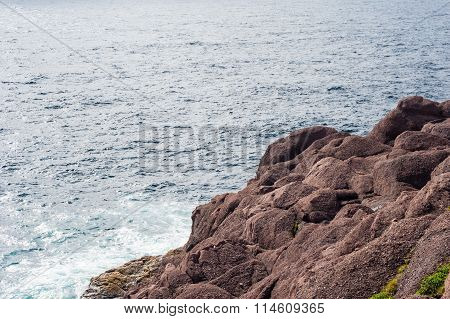 Diagonal Red Rocks By Empty Wavy Water
