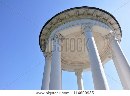 Gazebo With White Columns Against The Sky