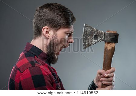 Strong young man with strange sharp hatchet