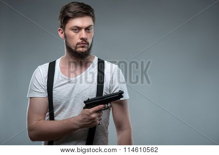Attractive young man is threatening with weapon