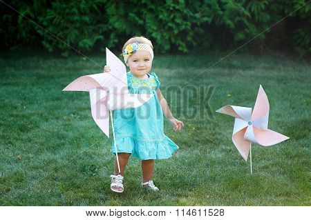 Happy Smiling Little Girl Standing On Meadow And Holding Toy White Pinwheel Windmill