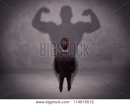 A young salesman standing with his back, looking at his musculous shadow reflecting on the wall concept