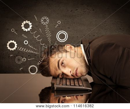 Falling apart illustration concept with cranks, cog wheels springing from a fed up and tired businessman's head resting on laptop keyboard