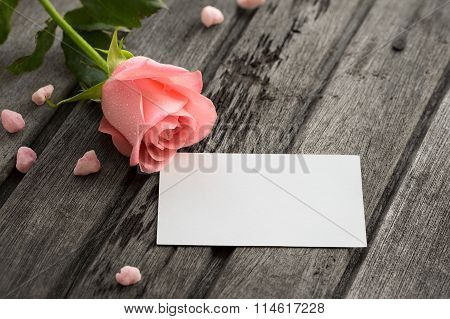 Pink Rose With Blank Envelope And Small Pink Decoration On Wooden Background