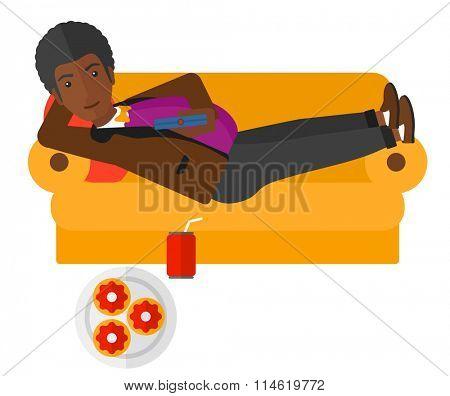 Man lying on sofa with junk food.